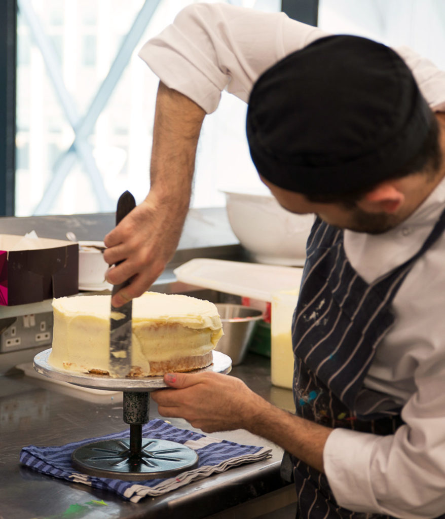 Decorating a cake during a Premium Kitchen Day Experience