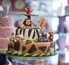 Zoo cake with lion, monkey, zebra and snake on top